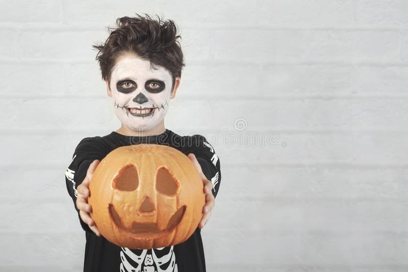 Happy Halloween.funny child in a skeleton costume with halloween pumpkin. Against brick background royalty free stock image