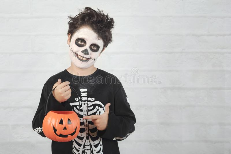 Happy Halloween.funny child in a skeleton costume with halloween pumpkin. Against brick background stock image