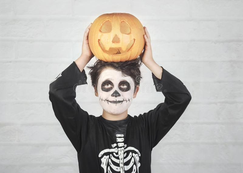 Happy Halloween.funny child in a skeleton costume with halloween pumpkin over on his head. Against brick background royalty free stock photo