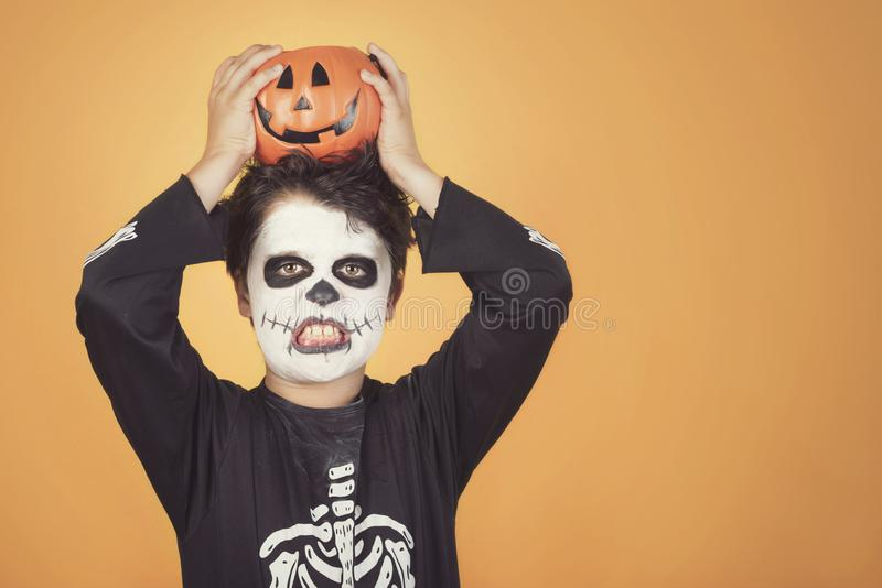 Happy Halloween.funny child in a skeleton costume with halloween pumpkin over on his head. Against orange background royalty free stock photography