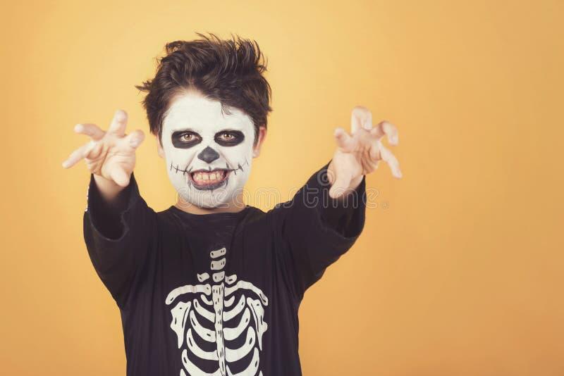 Happy Halloween. funny child in a skeleton costume of halloween. Over orange background stock photo