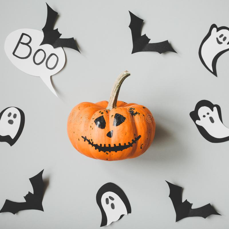 Happy halloween. Funny halloween pumpkin with paper bats and ghosts on gray background.  royalty free stock images