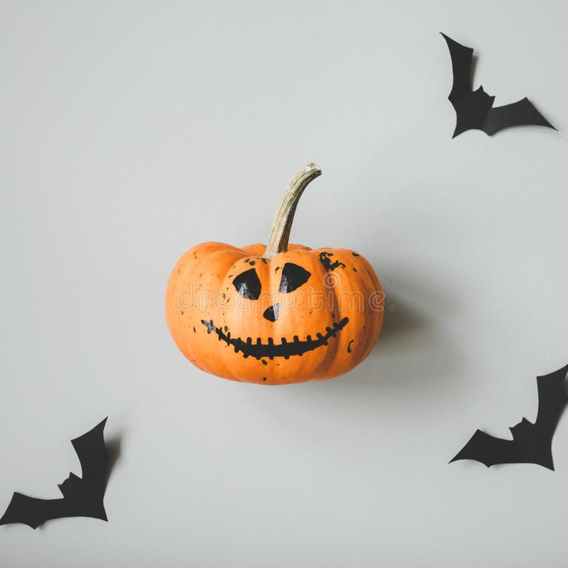 Happy halloween. Funny halloween pumpkin with paper bats on gray background.  royalty free stock photos