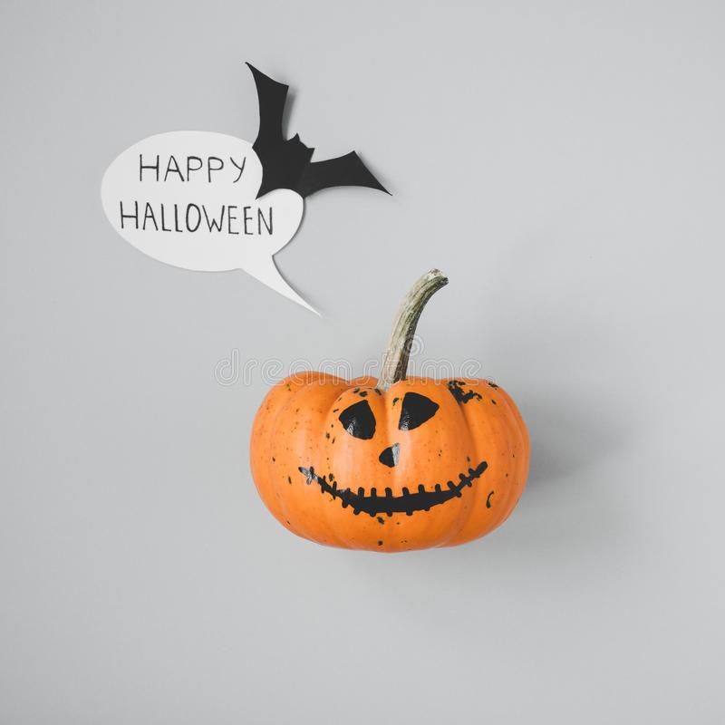 Happy halloween. Funny halloween pumpkin with speech bubble and bat on gray background.  stock images