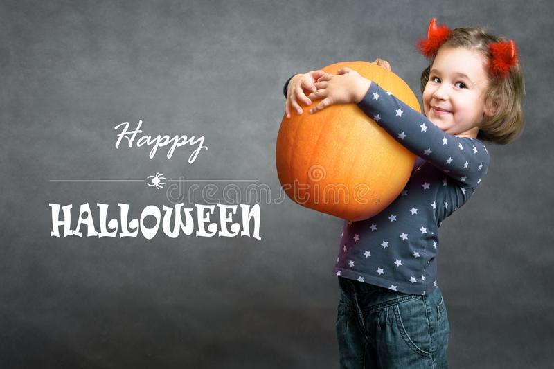 Happy Halloween! Funny little girl holds big pumpkin and smiles. Adorable child and Halloween typography royalty free stock image