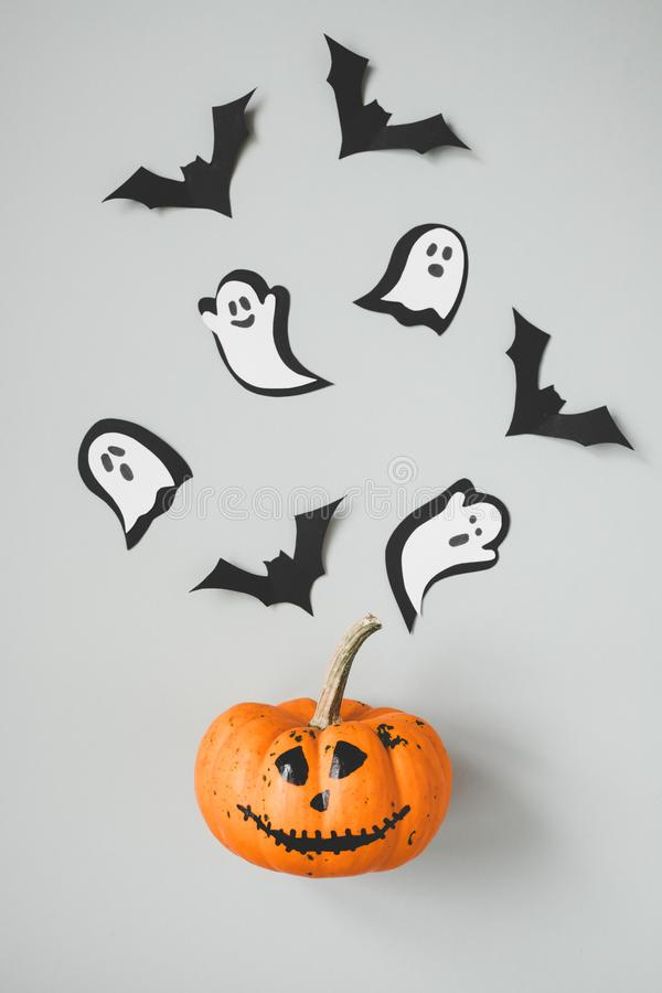 Happy halloween. Funny halloween pumpkin with paper bats and ghosts on gray background.  royalty free stock image