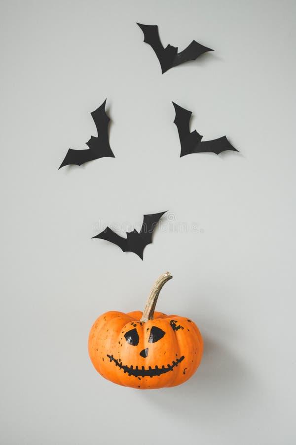 Happy halloween. Funny halloween pumpkin with paper bats on gray background.  stock photos