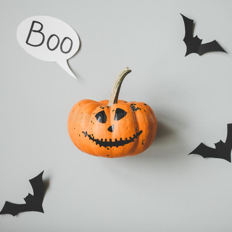 Happy halloween. Funny halloween pumpkin with speech bubble and paper bats on gray background.  royalty free stock photo