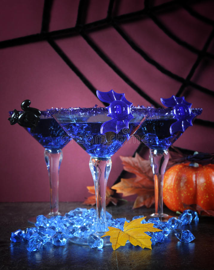 Happy Halloween ghoulish party cocktail drinks with blue martini glasses. Happy Halloween ghoulish party cocktail drinks with spider web and decorations on royalty free stock photography