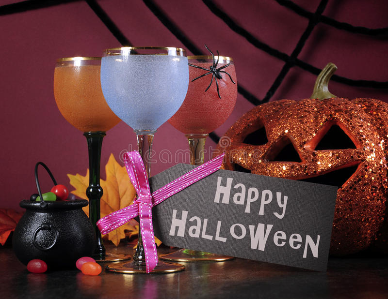 Happy Halloween ghoulish party cocktail drinks with greeting text. Happy Halloween ghoulish party cocktail drinks with spider web and decorations on purple stock images