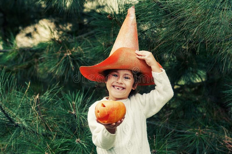 Happy Halloween . Girl with pumpkin and hat on the street. The child is holding a lantern made of pumpkin stock photo