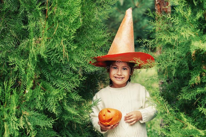 Happy Halloween . Girl with pumpkin and hat on the street. The child is holding a lantern made of pumpkin stock images