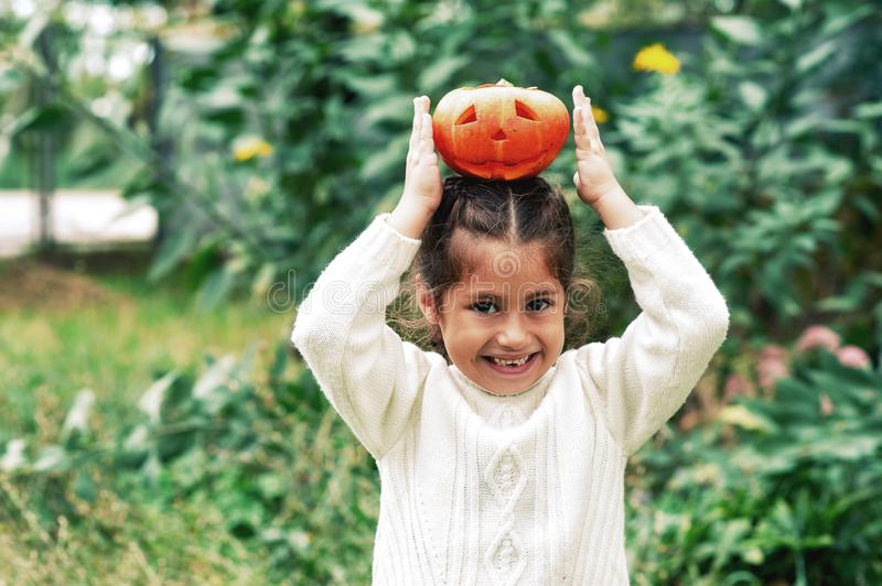 Happy Halloween . Girl with pumpkin and hat on the street . The child is holding a lantern made of pumpkin stock image