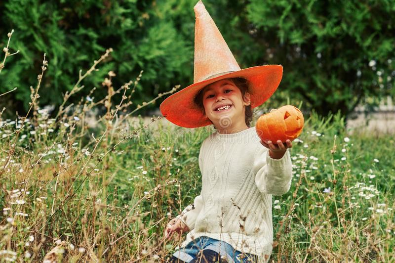 Happy Halloween . Girl with pumpkin and hat on the street. The child is holding a lantern made of pumpkin stock image