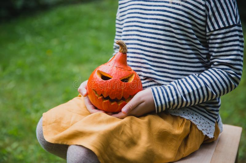 Happy Halloween. Girl seats on wooden chair and holds little pumpkin Jack O Lanterns outdoors. Autumn stock image