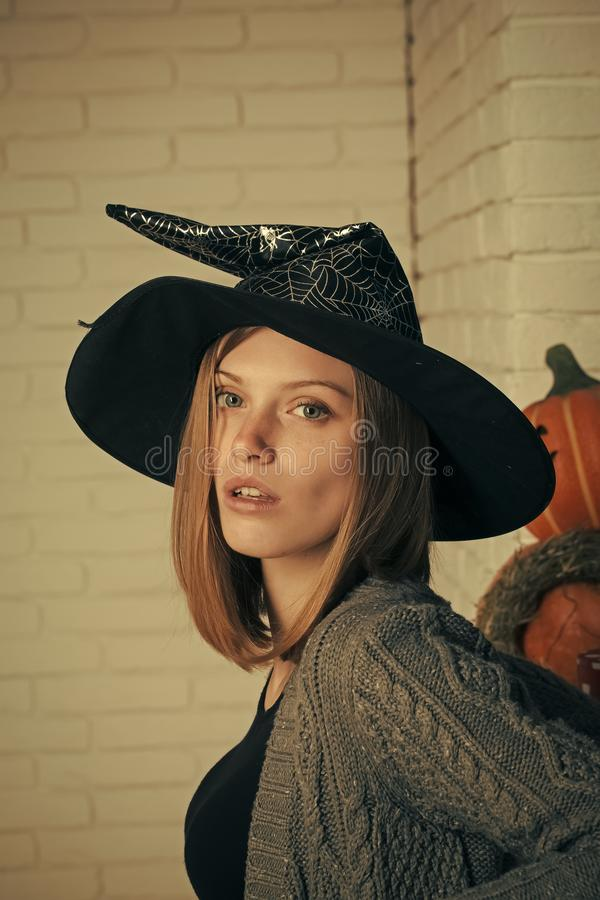 Happy Halloween. Halloween girl in witch hat. Woman with red hair and no makeup on face. Pumpkins and straw wreath on white brick wall. Holiday celebration stock image