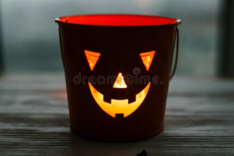 Happy Halloween. Glowing Jack-o-lantern face in dark. Spooky atmospheric jack o lantern glowing pumpkin bucket on black background. Trick or treat. Copy space royalty free stock image