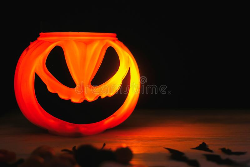 Happy Halloween. Glowing Jack-o-lantern face in dark. Spooky atmospheric jack o lantern glowing pumpkin bucket on black background. Trick or treat. Copy space royalty free stock images