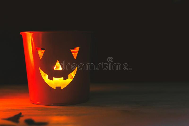Happy Halloween. Glowing Jack-o-lantern face in dark. Spooky atmospheric jack o lantern glowing pumpkin bucket on black background. Trick or treat. Copy space stock image