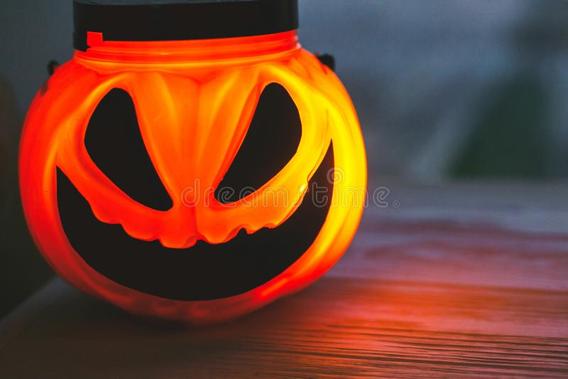 Happy Halloween. Glowing Jack-o-lantern face in dark. Spooky atmospheric jack o lantern glowing pumpkin bucket on black background. Trick or treat. Copy space royalty free stock photos