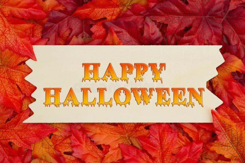 Happy Halloween greeting with fall leaves. Happy Halloween greeting, Some fall leaves and a wood sign with text Happy Halloween stock photography