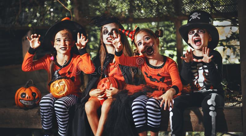 Happy Halloween! a group of children in suits and with pumpkins. In the forest royalty free stock photo