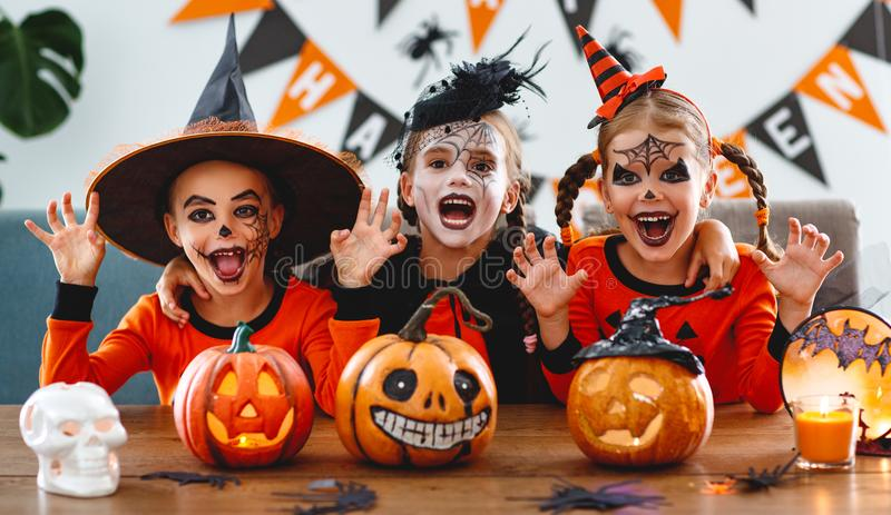 Happy Halloween! a group of children in suits and with pumpkins. In the home royalty free stock images