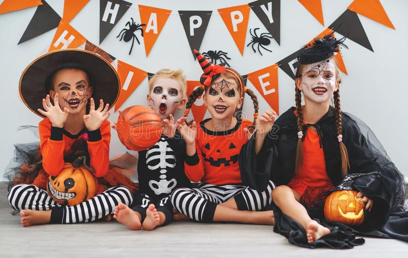 Happy Halloween! a group of children in suits and with pumpkins. In the home stock photos