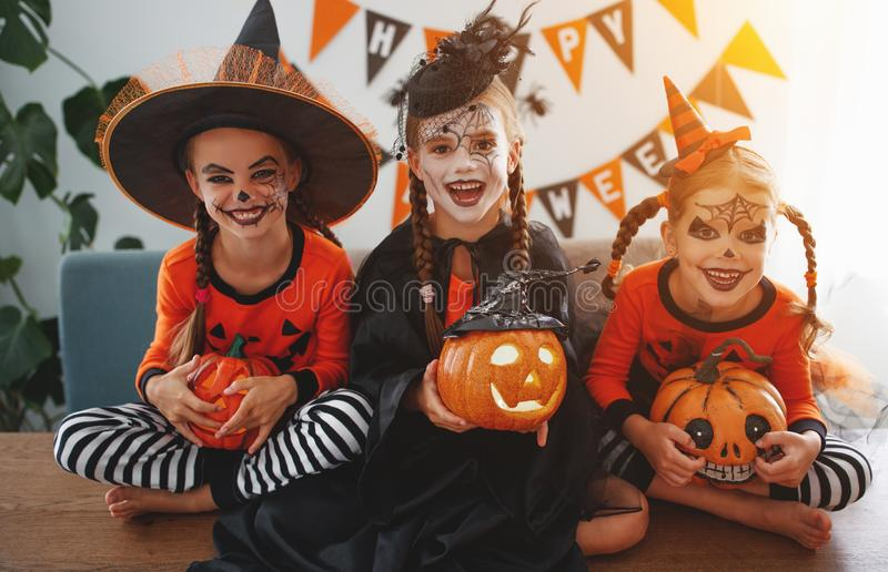 Happy Halloween! a group of children in suits and with pumpkins. In the home stock photography