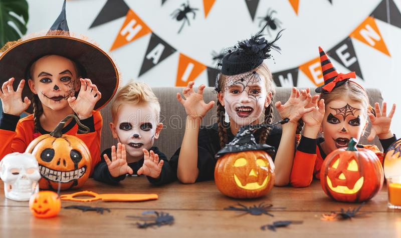 Happy Halloween! a group of children in suits and with pumpkins. In the home stock image