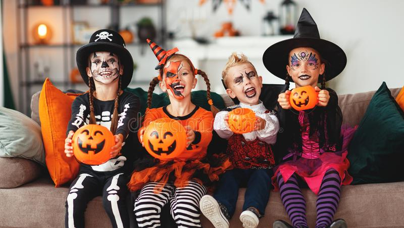 Happy Halloween! group of children in suits and with pumpkins in home stock photo