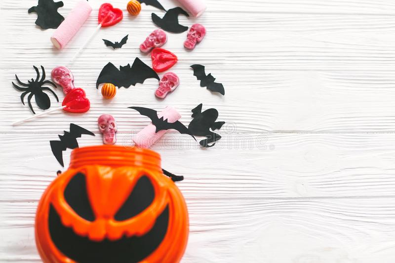 Happy Halloween. Halloween candy spilled from jack o lantern bucket with skulls, black bats, ghost, spider decorations on white. Wooden background, flat lay stock photography