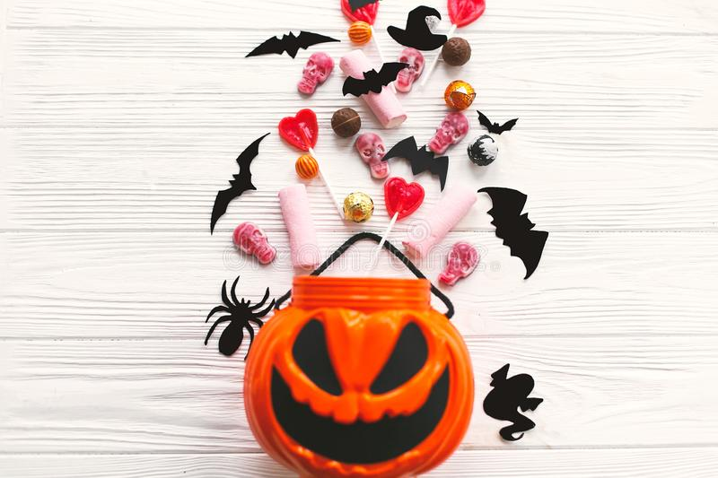 Happy Halloween. Halloween candy spilled from jack o lantern bucket with skulls, black bats, ghost, spider decorations on white. Wooden background, flat lay royalty free stock photos