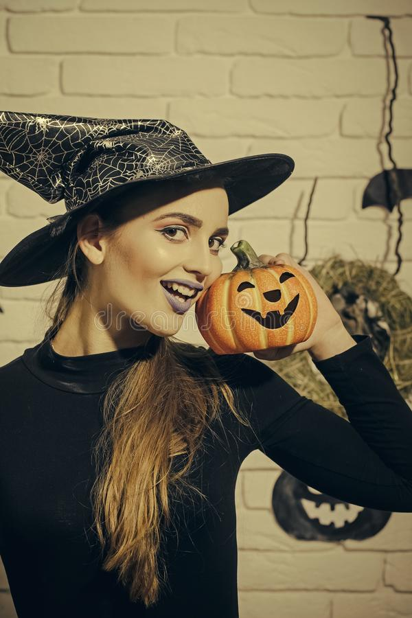 Happy Halloween. Halloween jack o lantern. Holiday celebration symbols on white brick wall. Woman smiling with blue lips and pumpkin. Mystery and horror stock images