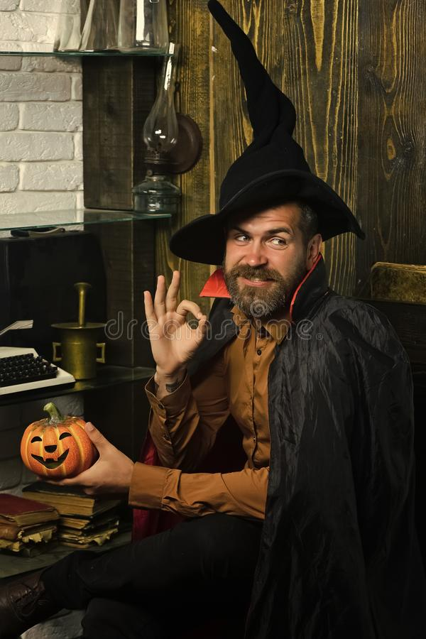 Happy Halloween. Halloween wizard smiling with pumpkin on wooden wall. Man in witch hat and cloak showing ok gesture. Wizardry and witchcraft. Magic and evil royalty free stock photos