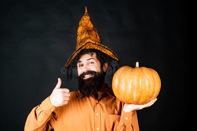 Happy Halloween - handsome man isolated. Happy Halloween. Smiling happy man with pumpkin. Young man with witch hat ready. To Halloween party. Trick or treat stock images