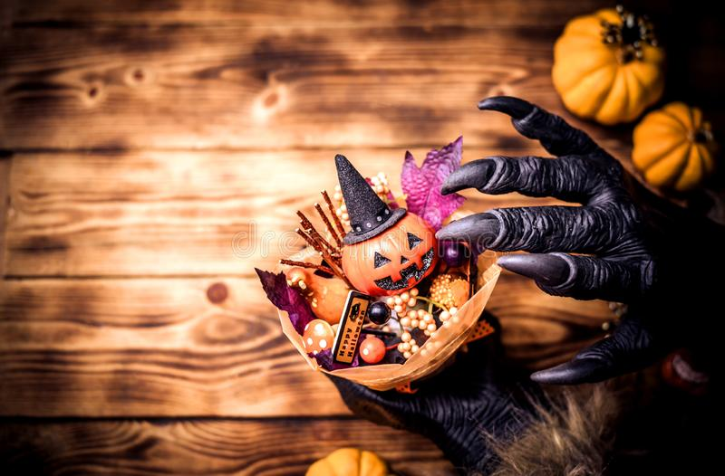Happy Halloween. Werewolf or zombie hands making scary pumpkin gift for trick or treat party. copy space for text royalty free stock photo