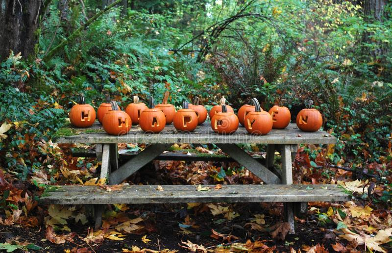 Happy Halloween Holiday Carved Pumpkins. Happy Halloween carved Jack O Lantern Pumpkins in a forest on a picnic table royalty free stock photography