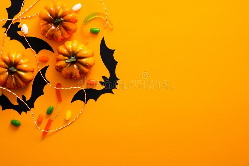 Happy halloween holiday concept. Halloween decorations, pumpkins, bats, candy, ghosts, bugs on orange background. Halloween party. Greeting card mockup with royalty free stock photo