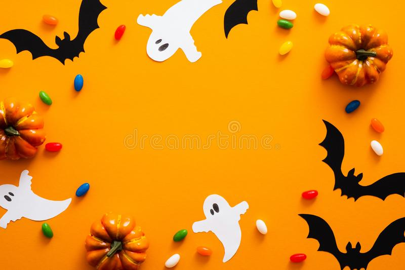 Happy halloween holiday concept. Halloween decorations, pumpkins, bats, candy, ghosts, bugs on orange background. Halloween party. Greeting card mockup with stock photography