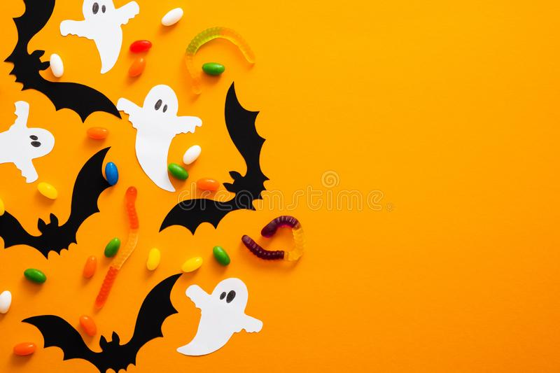 Happy halloween holiday concept. Halloween decorations, bats, ghosts, candy on orange background. Halloween party greeting card. Mockup with copy space. Flat stock photo