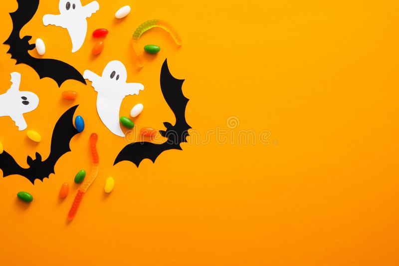 Happy halloween holiday concept. Halloween decorations, bats, ghosts, candy on orange background. Halloween party greeting card. Mockup with copy space. Flat stock photography