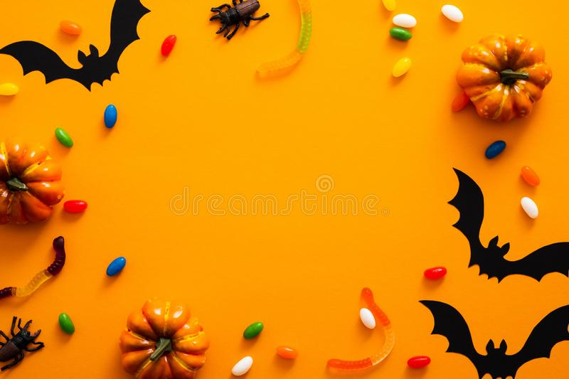Happy halloween holiday concept. Halloween decorations, pumpkins, bats, candy, bugs on orange background. Halloween party greeting. Card mockup with copy space royalty free stock photography