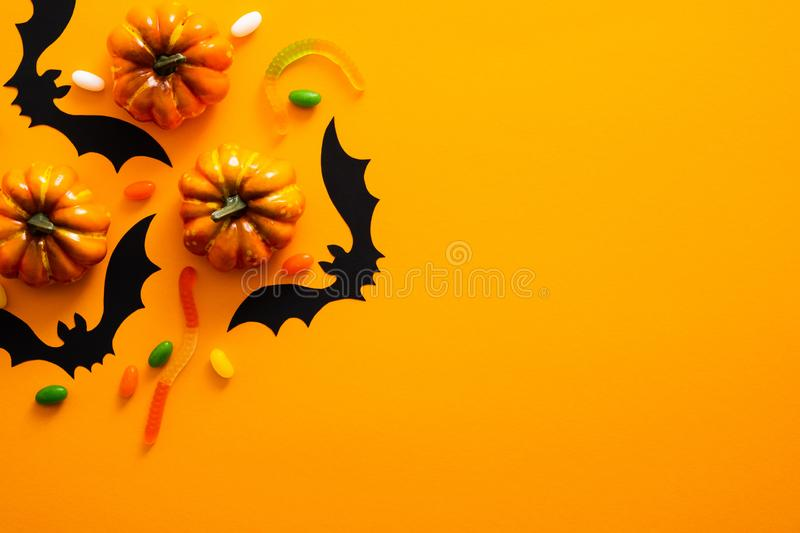 Happy halloween holiday concept. Halloween decorations, pumpkins, bats, candy, ghosts, bugs on orange background. Halloween party. Greeting card mockup with royalty free stock image