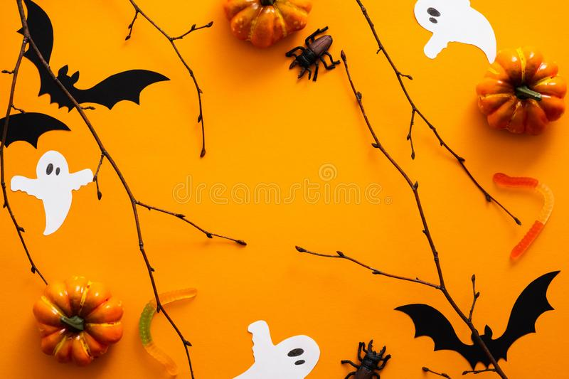 Happy halloween holiday concept. Halloween decorations, pumpkins, bats, candy, ghosts, bugs on orange background. Halloween party. Greeting card. Flat lay, top royalty free stock images