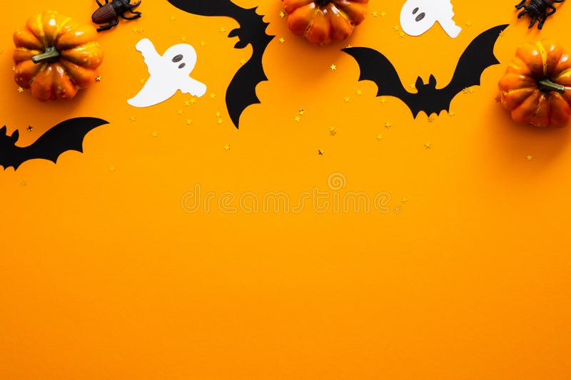 Happy halloween holiday concept. Halloween decorations, pumpkins, bats, ghosts on orange background. Halloween party greeting card. Mockup with copy space. Flat stock photos