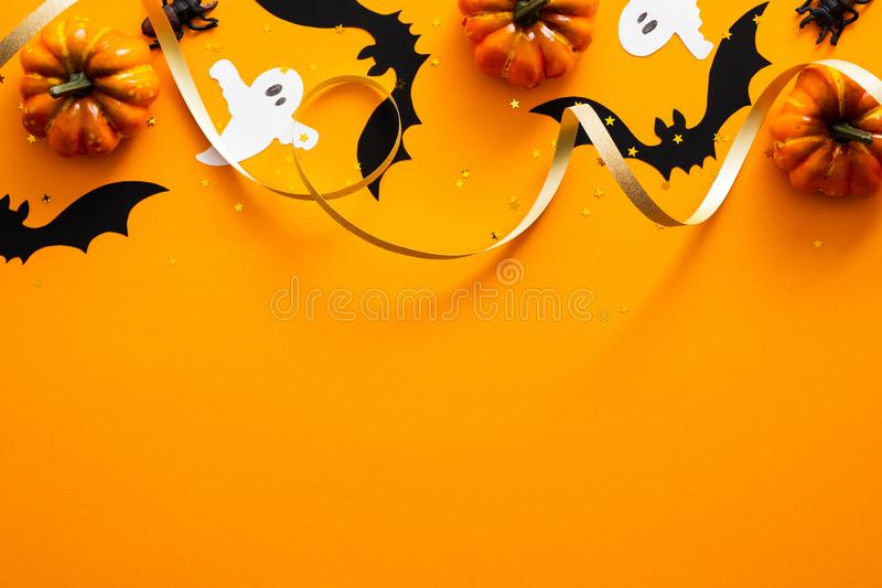 Happy halloween holiday concept. Halloween decorations, pumpkins, bats, ghosts on orange background. Halloween party greeting card. Mockup with copy space. Flat royalty free stock photography