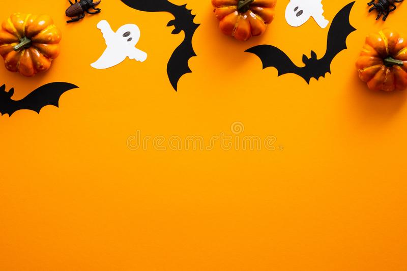 Happy halloween holiday concept. Halloween decorations, pumpkins, bats, ghosts on orange background. Halloween party greeting card. Mockup with copy space. Flat royalty free stock photos