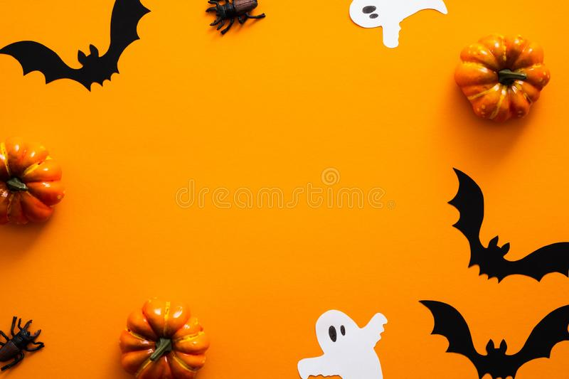 Happy halloween holiday concept. Halloween decorations, pumpkins, bats, ghosts, on orange background. Halloween party greeting. Card mockup with copy space stock images