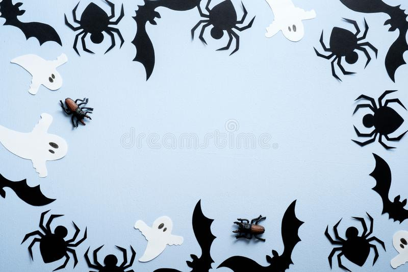 Happy halloween holiday concept. Halloween decorations, spiders, bats, ghost on blue background. Flat lay, top view, overhead stock images